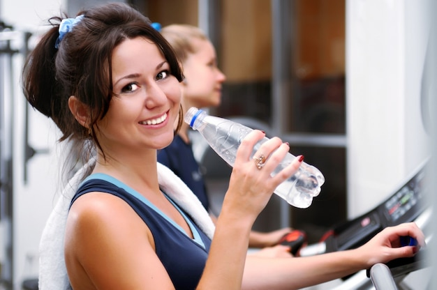 Adorable smiling brunette girl in sportswear and towel on neck posing with bottle of water