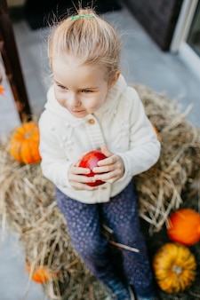 Adorable smiling caucasian baby toddler in white knittes jacket sitting on the haystack with pumpkins at porch and playing with apple.