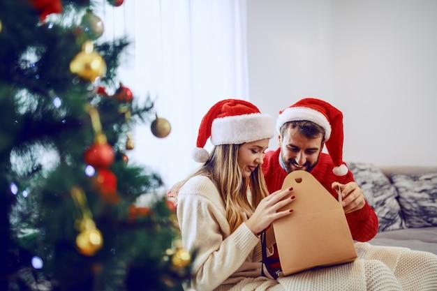 リビングルームのソファーに座っているとオープニングギフトの頭の上にサンタの帽子を持つ愛らしい笑顔白人カップル。手前にはクリスマスツリーがあります。