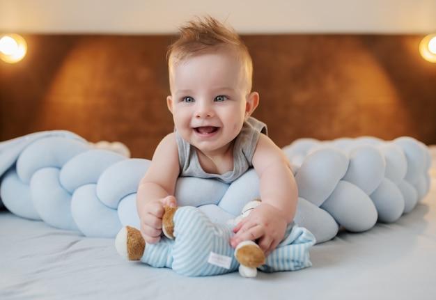 Прелестный улыбающийся кавказский маленький мальчик 6 месяцев лежал на животе на кровати в спальне и проведение плюшевого мишку.