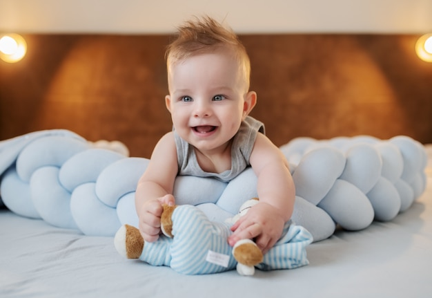 Adorable smiling caucasian little baby boy 6 months old lying on stomach on bed in bedroom and holding teddy bear.