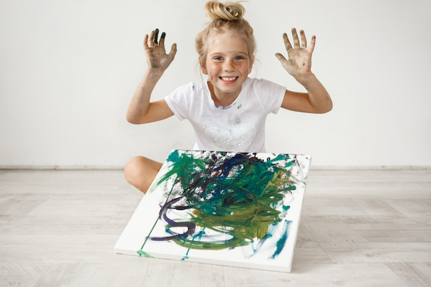 Adorable smiling caucasian little girl with hair bun wearing white cloth holding her hands up, sitting cross-legged with colourful picture on her legs. full of joy, cheerful blonde female kid.