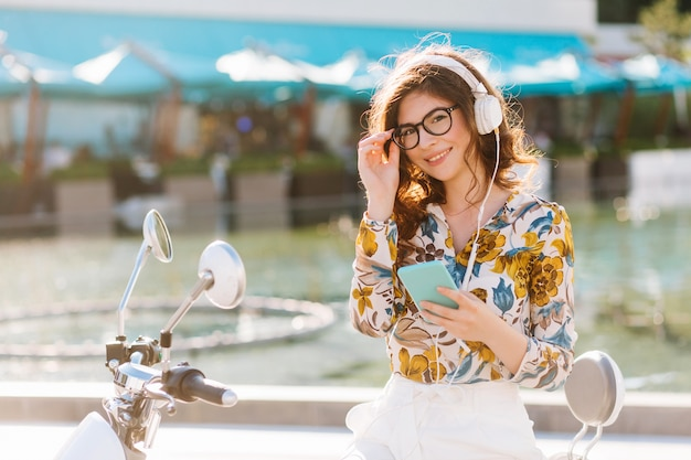 Adorable smiling girl looking with interest, holding her trendy big glasses and listening music