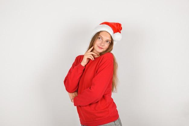 Очаровательная улыбающаяся девушка в красной шляпе санта-клауса в красном пуловере
