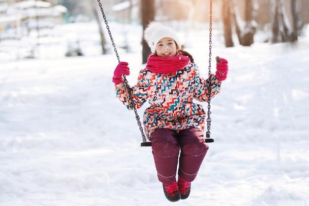 冬のブランコに乗って愛らしい笑顔の少女
