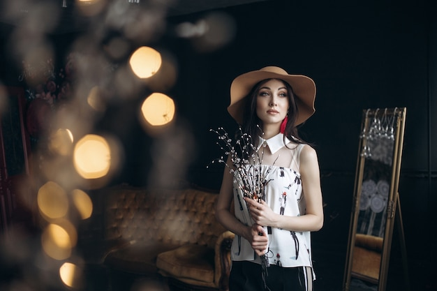 Adorable smiling woman in beige hat and with fashion look poses in the studio