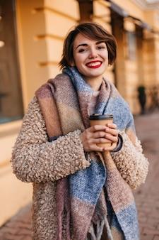 추운 날에 커피를 마시는 사랑스러운 웃는 여자