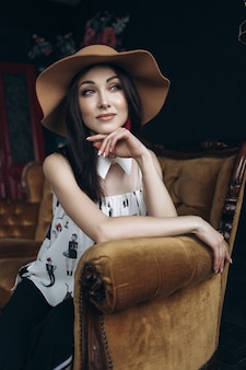 Adorable smiling woman looks like a lady sitting in a soft chair