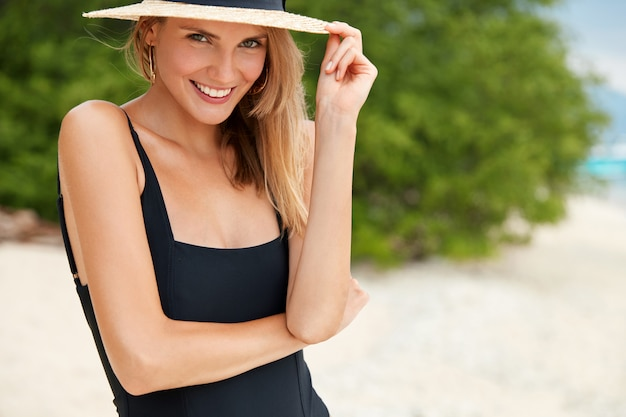 Adorable smiling young female wears swimming suit and hat, has walk across sandy coastline, satisfied with good rest. positiveness, happiness and relaxation concept.