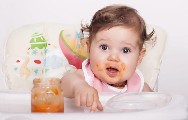 그녀가 좋아하는 음식을 먹는 사랑스러운 얼룩진 여성 아기