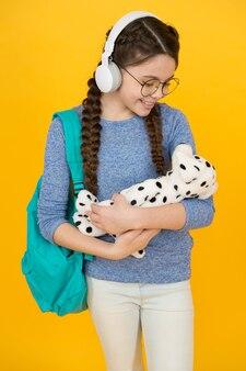 사랑에 빠지는 사랑스러운 부드러운 장난감. 행복한 아이가 장난감 개를 껴안습니다. 부드러운 장난감을 가지고 노는 어린 소녀. 장난감 가게. 선물 가게. 어린 시절 게임. 노는 시간. 사회적 기술을 개발합니다.