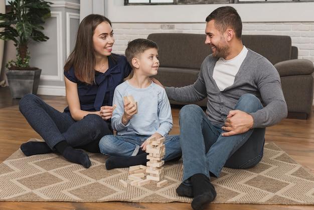 Прелестный сын играет с родителями