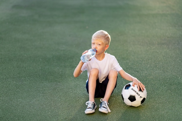 Adorable sporty child on the football field