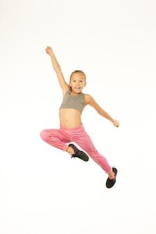 腕を上げて空中ジャンプしながら喜びで叫ぶ愛らしいスポーティな女の子。白い背景で隔離