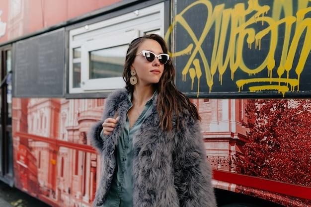 야외 사진 촬영 중에 포즈를 취하는 모피 코트를 입고 긴 물결 모양의 머리를 가진 사랑스러운 세련된 아가씨.