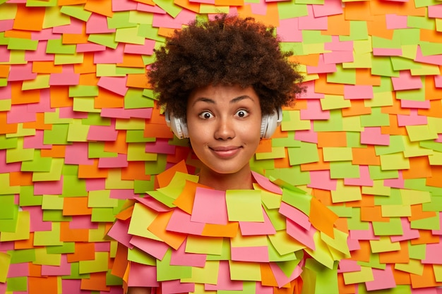 Adorable surprised dark skinned woman listens audio track, wears wireless headphones, enjoys favorite hobby, has amused shocked expression, models over paper wall with colorful adhesive notes