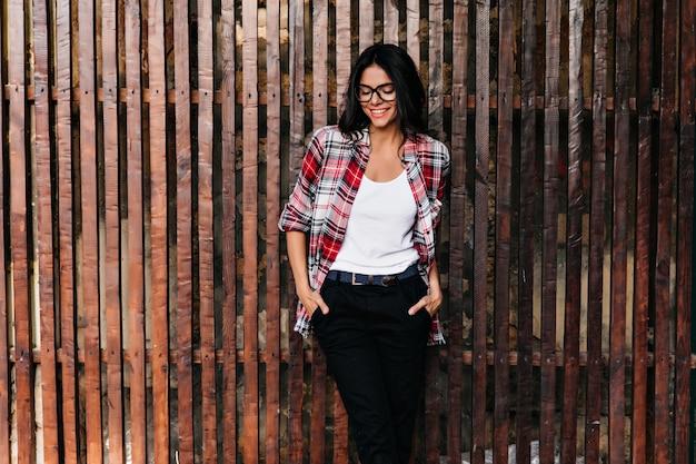 Adorabile modello femminile abbronzato che gode del servizio fotografico primaverile. ragazza caucasica di buon umore in bicchieri agghiaccianti all'aperto.