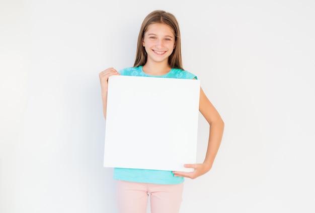 コピースペースのための空白の白い帆布を保持している愛らしい十代の少女
