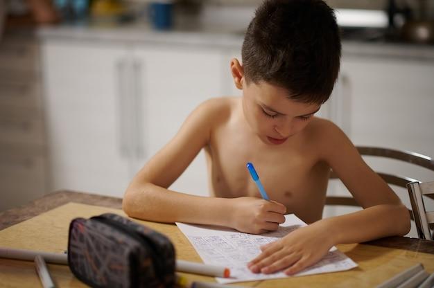집에서 흰 종이에 애니메이션 만화를 그리는 사랑스러운 10대 소년