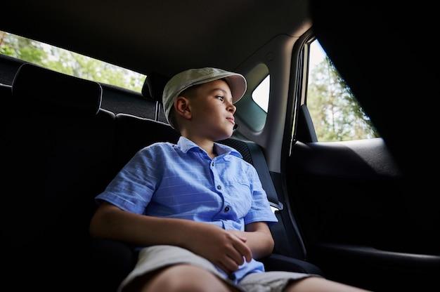 後部座席の車に座って窓の外を見ている愛らしい10代の少年