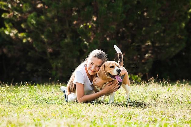 Очаровательная девочка-подросток играет с собакой породы бигль в парке