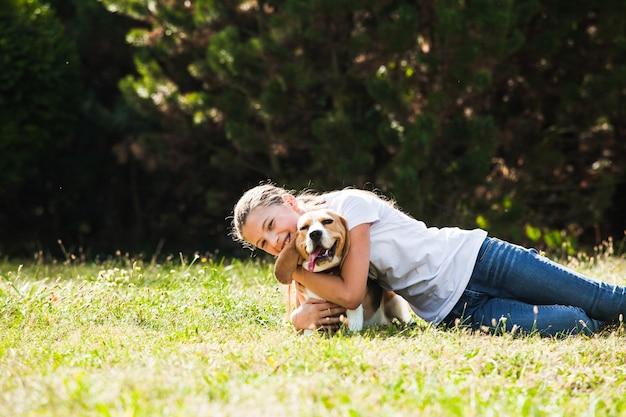 愛らしい10代の少女が公園でビーグル犬と遊ぶ