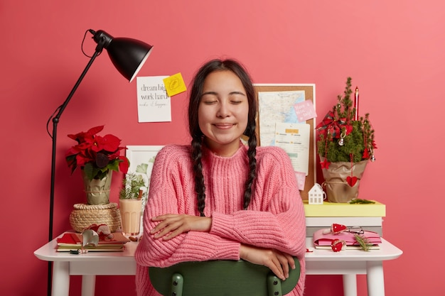 Adorable teenage girl with asian appearance, two braids, keeps eyes closed while sits on chair, imagines something wonderful happened during christmas time