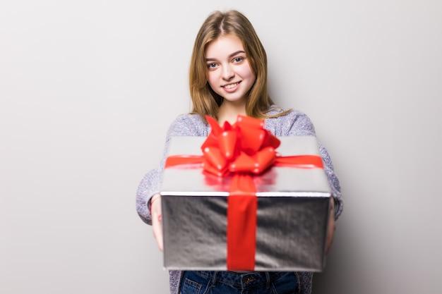Очаровательная девочка-подросток с большой подарочной коробкой