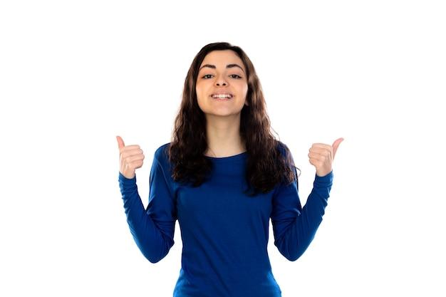 흰 벽에 고립 된 파란색 스웨터와 함께 사랑스러운 십 대 소녀