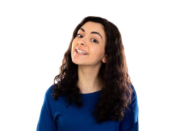 Очаровательная девочка-подросток с синим свитером, изолированным на белой стене