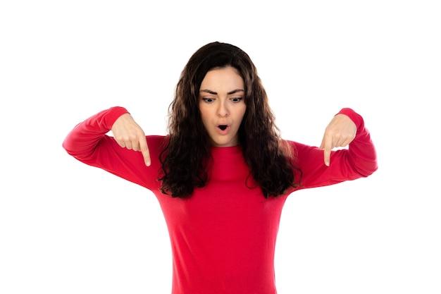 白い壁に分離された赤いセーターと愛らしい10代の少女