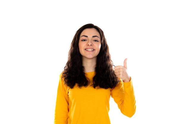 흰 벽에 고립 된 노란색 스웨터와 사랑스러운 십 대 소녀