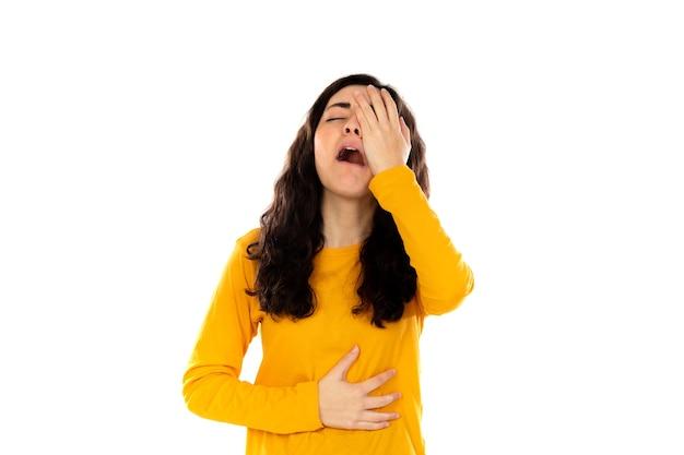 白い壁に分離された黄色のセーターと愛らしい10代の少女