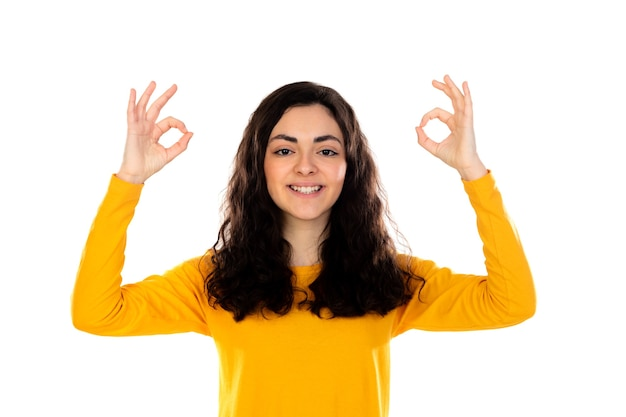 Adorable teenage girl with yellow sweater isolated on a white wall