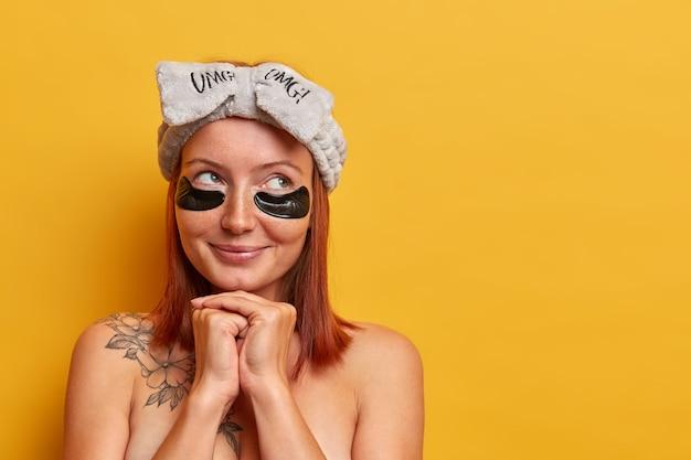 Adorabile donna premurosa con i capelli rossi, sta nuda al coperto, gode di trattamenti di bellezza, indossa cerotti di collagene per il recupero di idrogel per rimuovere occhiaie e borse sotto gli occhi, ringiovanisce la pelle.