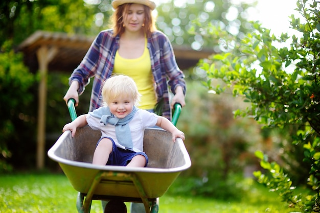 Adorable toddler boy having fun in a wheelbarrow pushing by mum in domestic garden on warm sunny day. active outdoors games for kids in summer.