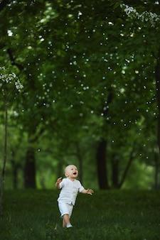 Очаровательный мальчик малыша гуляет по зеленой траве под цветущим деревом в городском парке.