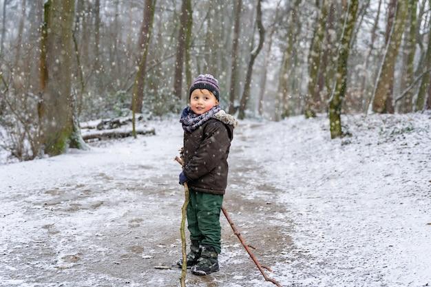 冬に公園を歩いている愛らしい幼児の男の子。暖かい服を着た子供は森の中で木の棒で遊んでいます。雪を楽しんでいる子供。