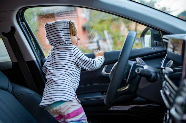 사랑스러운 유아 아이는 현대 고급 자동차의 운전석에서 운전을 합니다. 부모 개념과 같은 젊은 운전자 개념