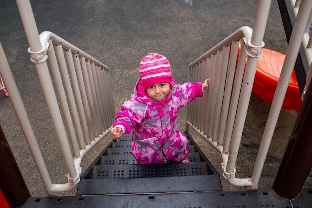 사랑스러운 유아는 놀이터에서 계단을 올라갑니다. 방한복을 입은 유아 아기. 가을이나 겨울, 추운 계절
