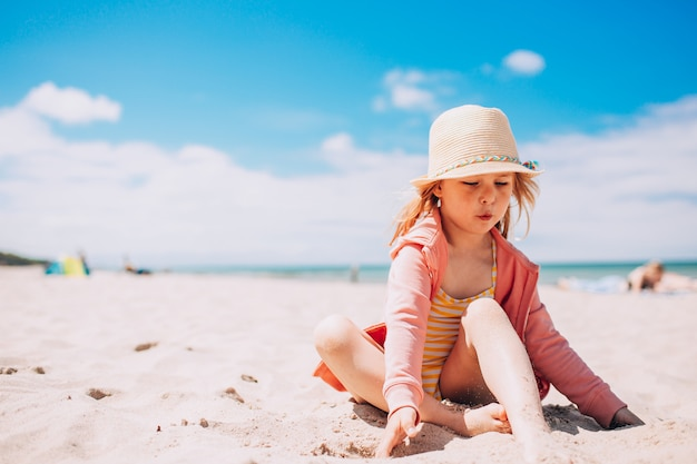 Adorable toddler girl in hat playing on white sand beach at the beach. summer, vacation.