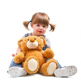 Очаровательная малышка обнимает плюшевого мишку