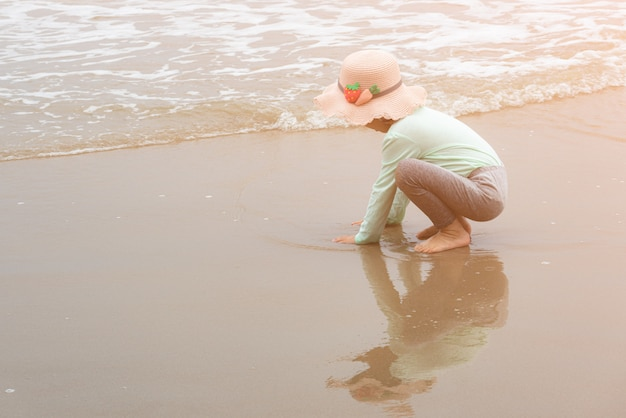 Adorable toddler girl playing with beach toys on sand beach