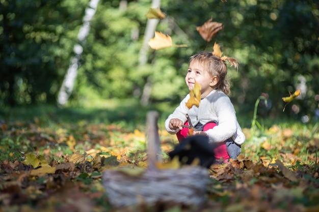 가을 공원에 앉아서 놀고 떨어지는 노란 낙엽 속에서 웃고 있는 사랑스러운 어린 소녀