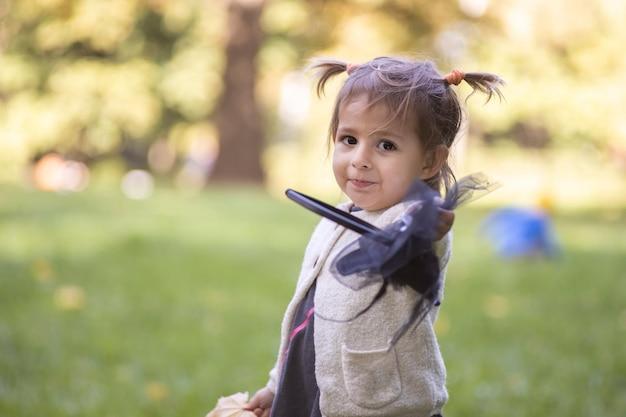 가을 공원에서 카메라를 보며 미소 짓고 마녀 모자를 들고 있는 사랑스러운 소녀
