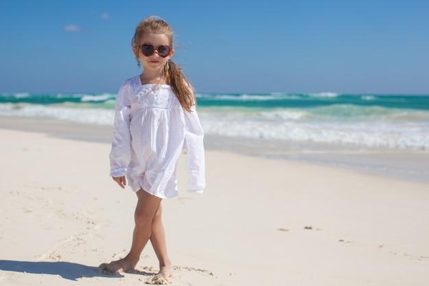 Adorable toddler girl in white dress walking at exotic beach