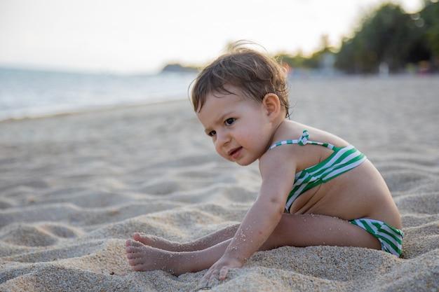 Очаровательный малыш в купальнике сидит на песчаном пляже в лучах солнца.