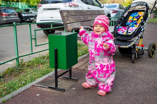 Очаровательный малыш выбрасывает мусор в мусорное ведро