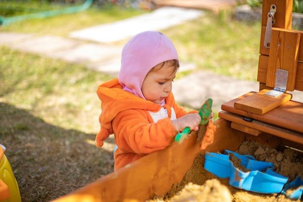 샌드박스에서 노는 사랑스러운 유아 여우 잠옷을 입은 귀여운 아이가 의 모래 초상화에서 놀고 있습니다