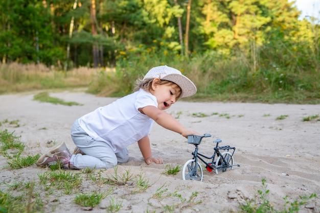愛らしい幼児は、自然の中でおもちゃの自転車で遊んでいます。芝生の砂の中で四つんばいの子供。